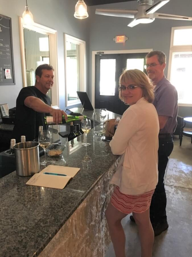 Steve Newsom serving Trilogy Cellars wines to Laurie and Shelly Ware