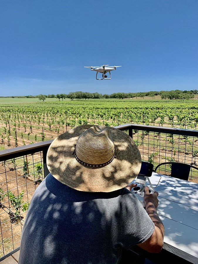 Reagan Sivadon, winemaker and a proprietor of Sandy Road Vineyard using a drone for vineyard photos